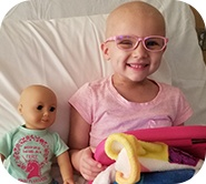Kinsley smiling on bed with her doll