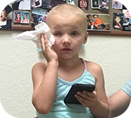 Kinsley holding a phone and and a handkerchief on her face