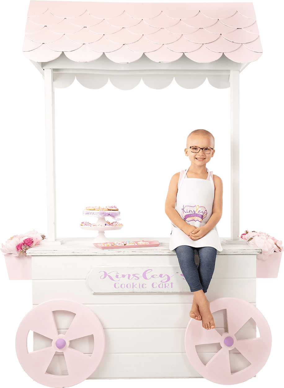 Kinsley sit on her cookie cart