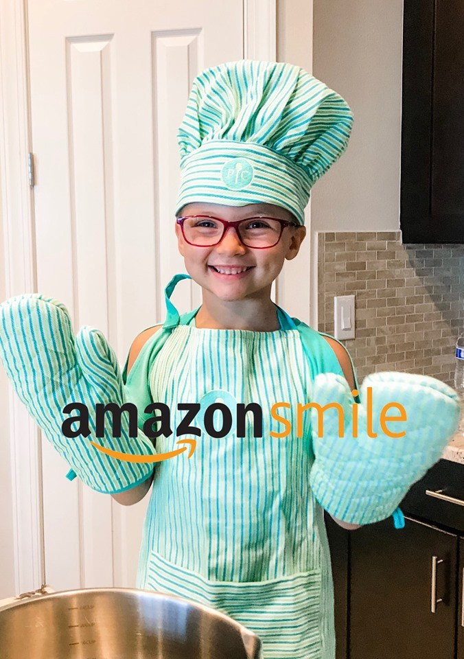 Kinsley wearing an apron, oven mitts and a chef hat