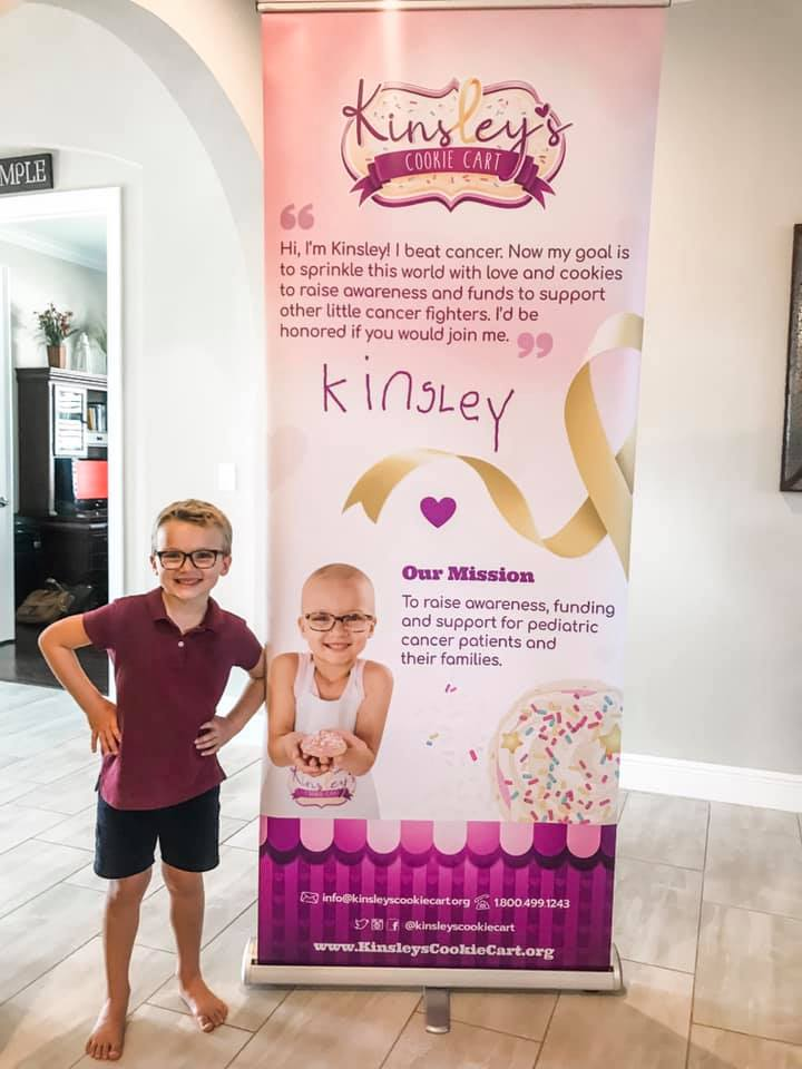 Kinsley standing next to her new pull up banner