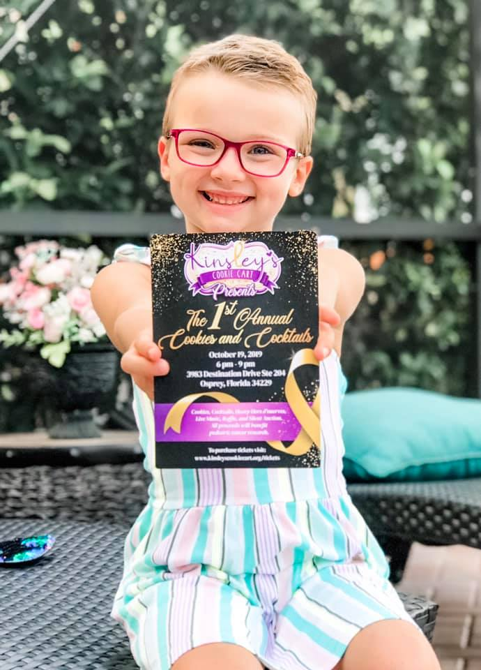 picture of Kinsley holding a Cookies & Cocktails invitation