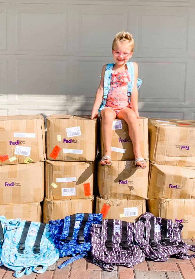 Kinsley sitting on a stack of boxes