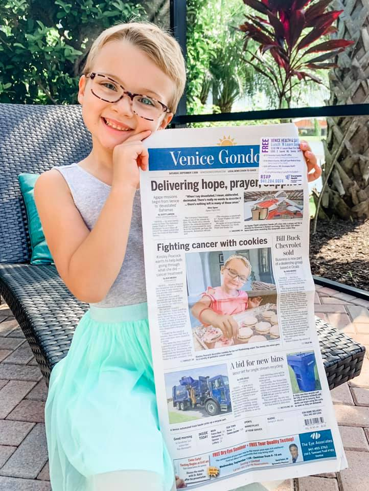 Kinsley-holding-a-newspapper-with-her-picture
