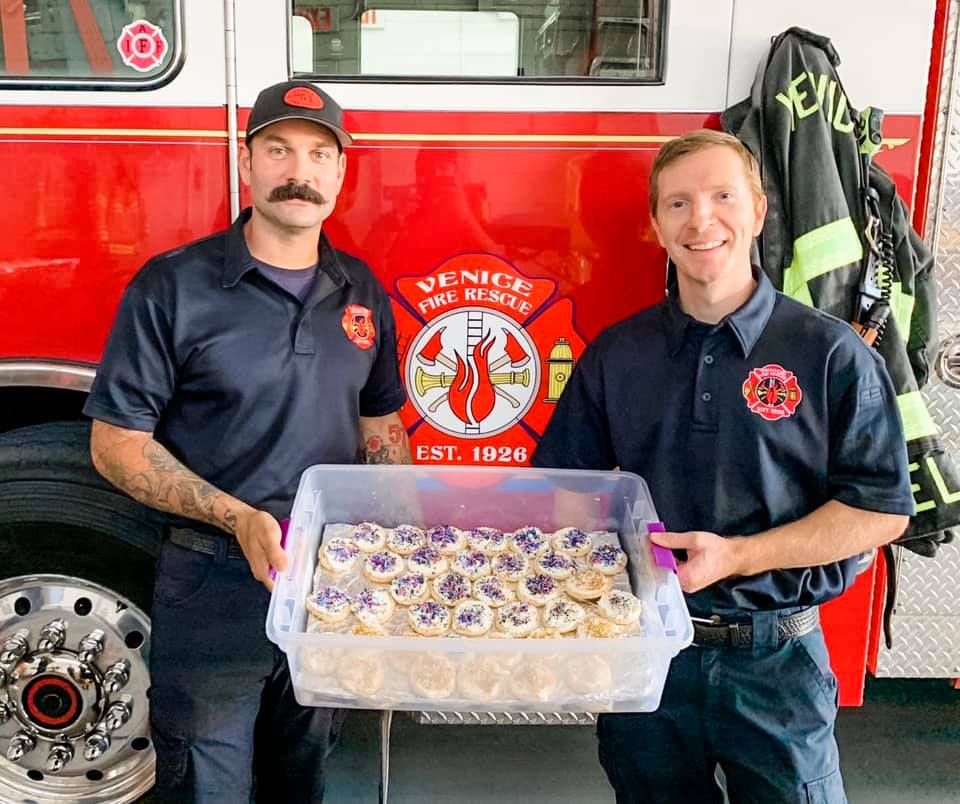 Two firemen holding a container full of Kinsley's cookies