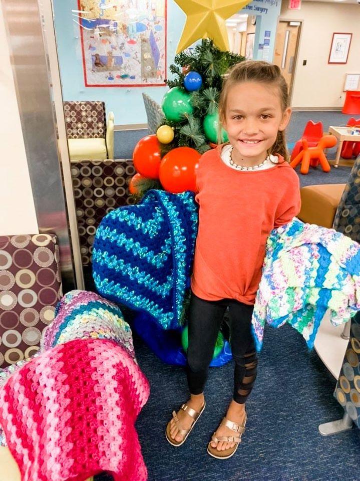 LIttle girl holding some blankets