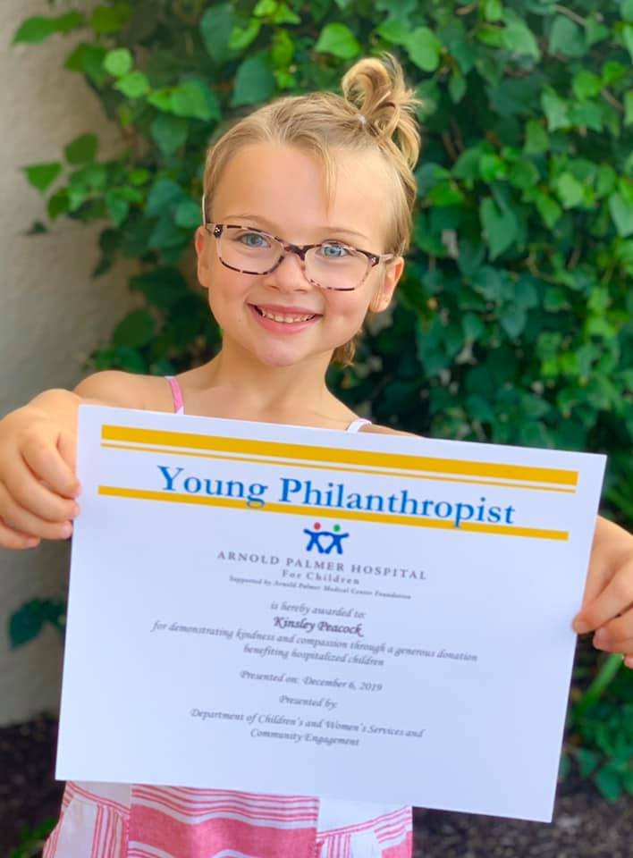 Kinsley holding the Young Philanthropist award